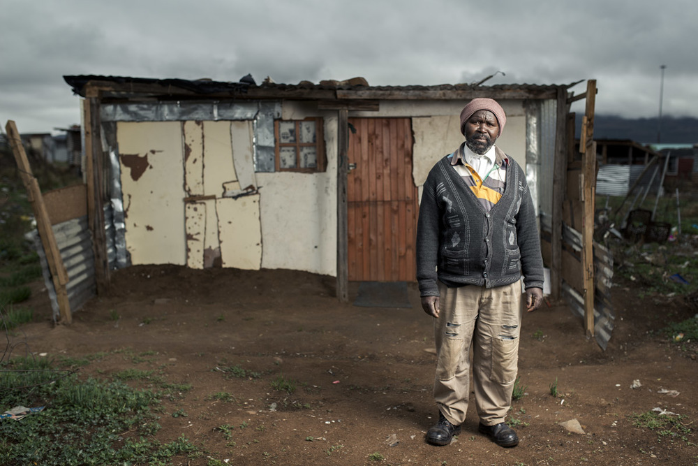 Mthuthuzeli Mtshange infront of his shack on the outskirts of Queenstown, Eastern Cape