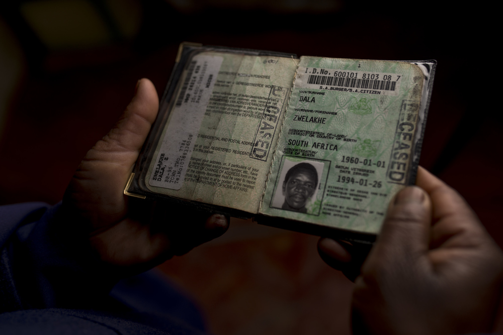 "Mrs Dala holding her husbands ID book stamped ""DECEASED"""